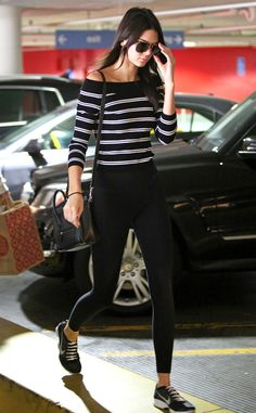 The model dresses comfortable for a day of shopping wearing a black striped boat neck top, leggings and Nike Flyknit sneakers.