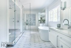 This crisp white bathroom is light, bright, and serene. The glass shower almost looks as if it is floating on air. Interior design by Hollester Interiors, Architecture by Vincent Burin Architects, Photography by Nat Rea