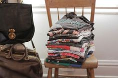t shirts piled on a chair - genius