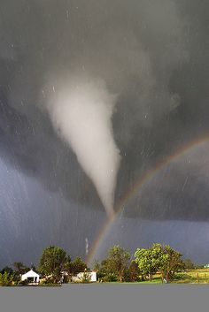Tornado and rainbow - During 2005 in Kansas, storm chaser Eric Nguyen photographed this budding twister. By coincidence, the tornado appears to end right over a rainbow. Streaks in the image are hail being swept about by the high swirling winds. All Nature, Science And Nature, Amazing Nature, Beautiful Sky, Beautiful World, Fuerza Natural, Wild Weather, Natural Phenomena, Natural Disasters