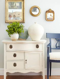 antique vignette.  beautiful white dresser, gold mirrors, collection of pottery, and blue side chair.