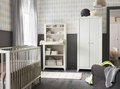 A nursery with a white crib combined with a wardrobe and cabinet with a changing table top.