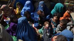 Afghan women and children sit in a truck
