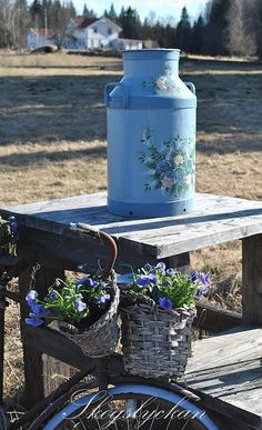 Nice display of country elements with farmhouse in the background - painted milk can and baskets with flowers in. #country #rustic