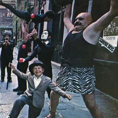 "The Doors - ""Strange Days"" - The cover includes a Fellini-esque mixture of amateurs/friends and professionals, a surrealist portrayal of that generation. Besides from the real acrobats, the others were just improvising: the trumpet player is a taxi driver given 5 dollars, the juggler is the photographer's assistant and the strongman was a club doorman.  This original idea was only put in practice after Jim Morrison repeatedly refused to appear on the album cover."