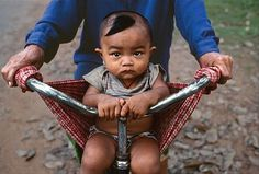 Artist: Steve McCurry, Baby in a Bicycle Sling, 2000, fuji crystal photograph