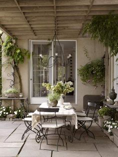 Timeless neutral patio with wooden pergola and metal bistro dining chairs.