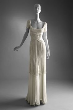 """Dress   Valentino Haute Couture PE 1993 - The Budellini technical material webs rolled into tubes and apply tulle, organza, chiffon or base. This technique is wonderful to accentuate an hourglass shape  The  '' Budellini """" fringe bands around the knee with dangling beads at the end of each fringe. Below, a chiffon skirt cascades cream upstairs."""