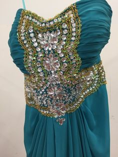 Teal prom dress with silver and gold aplique on top. Pleated waistline and draping back of... $97