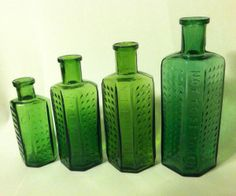 Four Green Glass English Poison Bottles. Casket shaped with embossing and hobnails. Green Glass Bottles, Blue Bottle, Glass Jars, Vintage Green Glass, Antique Bottles, Casket, Paper Weights, Perfume Bottles, Container