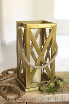 Lantern. Traditional Nautical Style arrives in our oversized lantern. Antiqued brass with rope accent conjures images of fine yachts. At over a foot tall, this lantern makes a statement atop the mantel or sofa table.