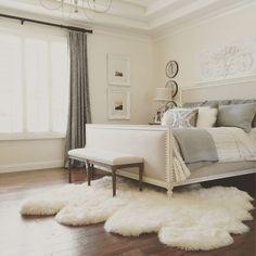 elegant master bedroom with restoration hardware bed, sheepskin rug, ballard design mirrors and plaque