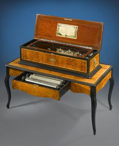 A captivating and exceptionally engineered Swiss Sublime Harmonie six cylinder music box with matching table. Set in a beautiful case of burled walnut with satinwood and ebonized wood inlay, this piece serves not only as melodious entertainment but also as a fine example of Victorian furniture.