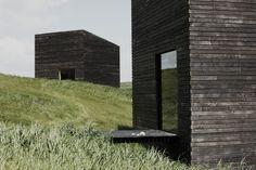 Blackened timber Eyrie cabins are tucked into the slopes of a ...
