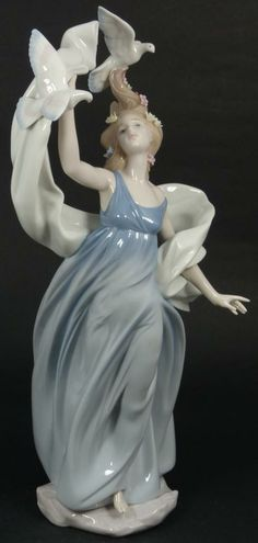 """Lladro Spain figure depicting a woman with doves. Titled """"New Horizons"""" Number 6570. Has a glazed finish. Includes original box. Issued in 1999 and retired in 2000. Part of the inspiration millenium collection. Has a current market value of $300.00 to $690.00."""