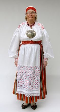 Tarvastu woman's suit belonged to the 19th century from fine linen shirt, along a striped woolen skirt or linen pallapool linen robe, long-cloak, coat, apron, belt, Tar- coif or Mulk towel, wide in the calf portion of stockings, gloves, and as footwear the shoes.