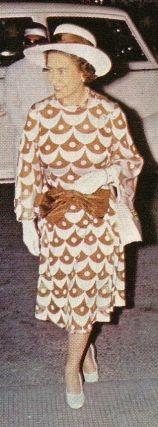 The queen in a dress with coffe and cream scallop pattern and accessories