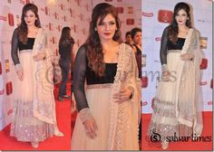 Bollywood actress Raveena Tandon in designer Anarkali kameez with black yoke and netted full sleeves.It's embellished with mirror work on hem and border.Paired with churidaar salwar and matching net dupatta with mirror work and lace border from designer Manish Malhotra.