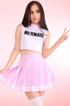 "Pale pink high-neckline crop top that says ""MERMAID"" across the chest in black"