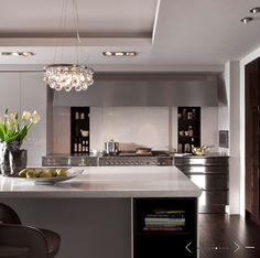 source: de Giulio Kitchen Design   Modern, contemporary kitchen design with hidden sliding doors pantry, kitchen island with quartz countertops and Ochre Arctic Pear Chandelier