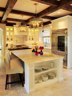 This open Old World style kitchen features a beautiful marble island, exposed wooden beams and intricate chandeliers. A pop of color is added in the flower vases on the island.