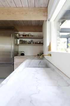 marble kitchen sink and brass faucet, wood beams and ceiling, modern window, open shelving