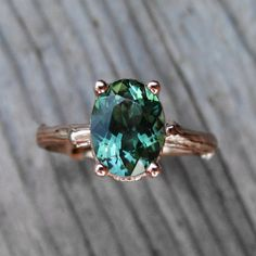 A real twig is cast in solid recycled gold to create the unique ring shank. Set upon the branch is a sparkling tourmaline in a rich blue-green hue.