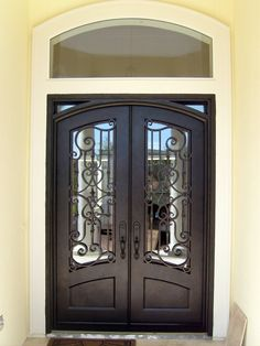 Here is another compromise for people who would like arch top doors, but have a straight top frame.These homeowner chose clear glass behind their scroll work to compliment their clear glass transom.  home building, front doors, iron doors, wrought iron doors, entry doors, dream home, custom doors, home construction.