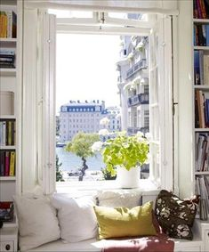 This cozy window seat reading nook has a giant picture window, complete with a city view and flanked by built-in bookshelves. Stunning!