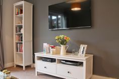 Our Living Room - ideas - grey walls - TV mounted - mustard accent - wooden coffee table - ikea white furniture - flowers - bookcase - TV unit