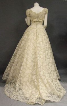 """1950's Wedding Gown with """"Saks Fifth Avenue"""" label. Short sleeved bodice with an ivory silk taffeta band and tiny faux pearl beading. Closes down the back with 31 covered buttons."""