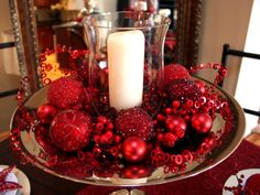 Love this concept for a Christmas centerpiece - lots of red textures on a pedestal tray with a stark white candle in the center.