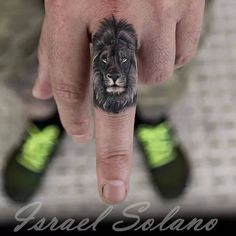 Black and grey lion tattoo on the left middle finger.