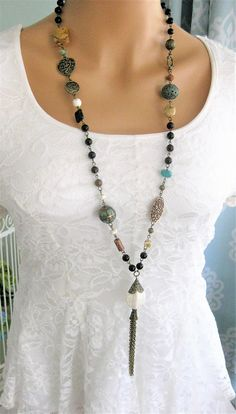 Bohemian black, brown, blue, and bronze beaded tassel necklace handmade by Ralston Originals. Brass chain tassel with black glass beads, natural stone beads, metal beads, and bronze links. This tassel necklace is 36 inches. Tassel length 3.5 inches. This bohemian tassel necklace is