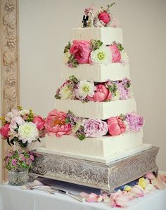 Pastel de boda blanco decorado con flores naturales en cada nivel.