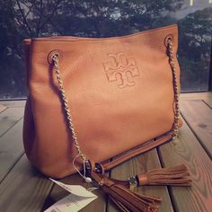 "Tory Burch Thea slouchy chain shoulder tote My last one Thea slouchy in this color. So no lowball offer thanks.  Leather and chain strap with 9"" (24.5 cm) drop. Height: 10"" (26 cm) Length: 13.5"" (34 cm) Depth: 6"" (15 cm) made of soft pebbled leather, with a strap that can be doubled or worn extra-long. Designed with a zippered interior compartment for your small essentials, it's a roomy silhouette that can effortlessly take you from work to weekend.  100% authentic and NWT, comes with…"