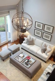 Wooden floor; white couch + grey cushions; gray table and side stools; four black picture frames; brown carpet; big window