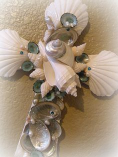 Majestic wall cross in lovely teals and whites..This cross is beautiful with its focal point of a grand white Spindel Shell and pearlized