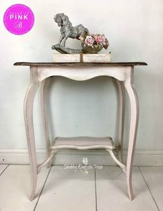 A pretty late Victorian occasional table hand-painted in pale pink with black wax added to give it a vintage shabby chic appearance. It has a little shelf at the bottom centred between the beautiful curved legs. The top has been stained with Jacobean Oak, washed with the pink of the base and then stenciled with a French design.