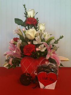 LOVE IS...   Item# VD04   As Shown $59.95     Show what you think love is by sending this arrangement that includes our freshly baked Otis Spunkmeyer cookies in a small heart basket along with a floral arrangement including lillies, white alstromeria, red carnations, and pink miniature carnations beautifully held together in a heart shaped container.     Ask us about upgrading your arrangement:   Deluxe $69.95   Premium $79.95     Limited Availability! $60