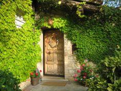 L'antico portoncino d'ingresso risalta tra il verde dei rampicanti