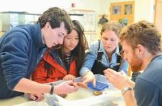 A SEA STAR CAPTURES the attention of students at a Chewonki Semester School. From left, are Evan Fischer, Lawrence Academy; Sharon Cheng, The Hotchkiss School; Casey Gaughan, The Thacher School, and Matt Weeks, Chewonki Traveling Natural History instructor.  PHOTOS / CHRIS PERCY