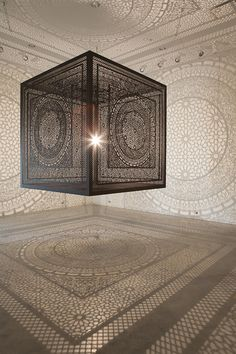 Ornately carved wood cube projects shadows onto gallery walls