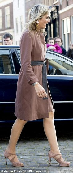 A polished Maxima paired her sophisticated outerwear, which had a grey lining and tie-waist belt, with high heels in a matching hue, a large silver cuff and flower-adorned earrings.