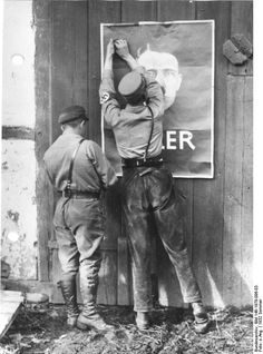 Two German Nazi Party SA men putting up an election poster featuring Adolf Hitler, Mecklenburg, Germany, summer 1932 German Federal Archive.