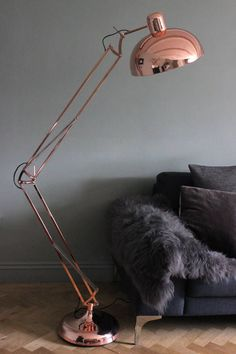 Copper angled floor lamp against a dark grey faux fur throw is just divine in this living room. Modern, stylish but super cosy.