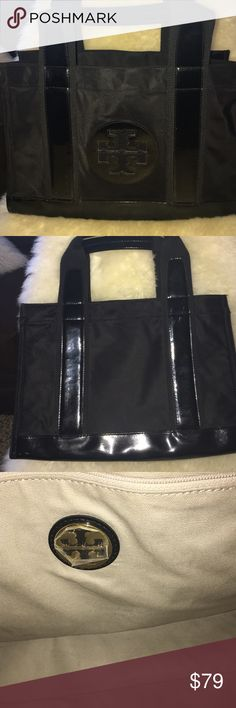 """Tory Burch Black Canvas/Patent Leather Tote Bargain! Tory Burch Medium Tote in Black Canvas with Black Patent Straps and Trim. Tory Burch Logo on outside and Gold metal logo on Inside. Two Zippered Pockets Inside. Open top. Bag Dimensions: length 13.5"""", height 9.5"""", depth 5"""", strap drop 4.5"""". CONDITION NOTES: There is Scratching on the patent trim on the front of the bag but it doesn't stand out just shows in the turn of the light. If you want more pics let me know. The bag is priced to…"""