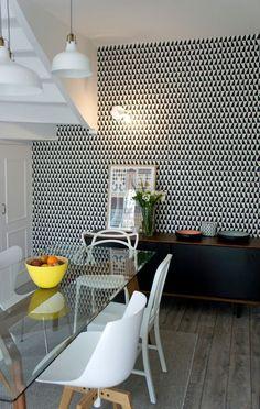 Vue sur la salle à manger, on aperçoit le mur graphique noir et blanc.