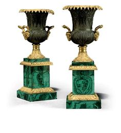 A PAIR OF RUSSIAN ORMOLU, PATINATED-BRONZE AND MALACHITE VASES CIRCA 1840-1850 Each with a campana-shaped vase, the everted lip mounted with beaded lambrequin decoration, the body chased in the Gothic taste, and the acanthus-cast shaped handles decorated with ram's heads, on a gadrooned and foliate-cast square stand, one with inscription 'W18732 113 V(?)' to the underside One: 14¾ in. (37.5 cm.) high, the other: 15 in. (38 cm.) high; each: 6 in. (15.5 cm.) diameter (2)