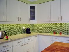 Color is a great way to add life to an inexpensive kitchen. The cabinets in this room by TS Kitchen Projects are from Ikea, and the ceramic tile was under $10 per square foot. Thanks to its bright green hues, the backsplash acts as a focal point for the room, making the space memorably playful.